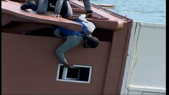 capsized tourist boat: witnesses report overcrowding; bahrain: bahrain port: ext divers on upturned hull of dhow al-dana diver under water next hull... - surfacing stock videos & royalty-free footage
