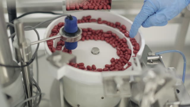 capsules being processed in a pill sorting machine - pharmaceutical manufacturing machine stock videos & royalty-free footage