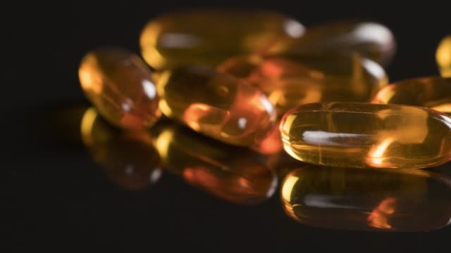 capsules omega 3 on black background - omega 3 stock videos & royalty-free footage