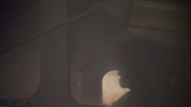 a captain can be dimly seen through the windows of a wheelhouse. - 館長点の映像素材/bロール