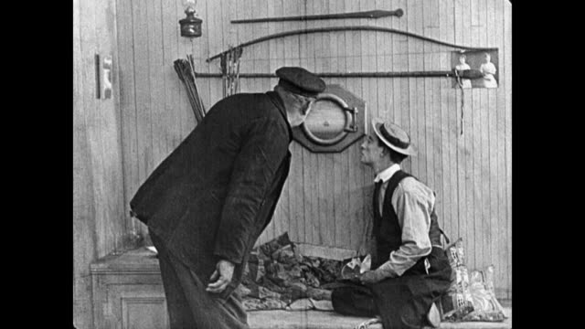 1923 captain (joe roberts) catches cabin boy (buster keaton) sighing longingly into porthole, takes it off the wall and gives it to him - 1923 stock videos & royalty-free footage