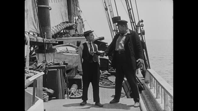 1923 captain (joe roberts) directs cabin boy (buster keaton) to go to the ship's port and he returns with a bottle of port wine - 1923 stock videos & royalty-free footage