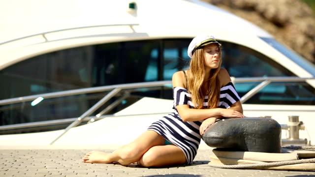 vidéos et rushes de capitaine fille reposant sur un bateau, à proximité de la jetée - capitaine de bateau