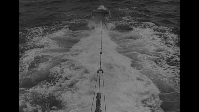 captain looks through binoculars / three men stand on submarine bridge / man climbs through hatch and closes it / vs men work with levers and gauges... - portello video stock e b–roll