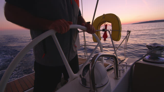 ws captain navigating a sailboat at sunset - captain stock videos & royalty-free footage