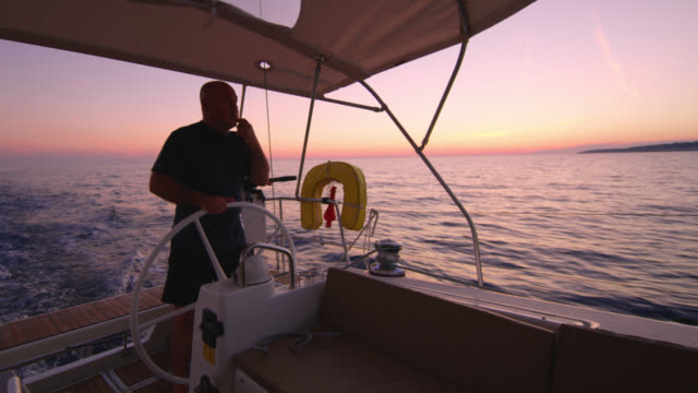 ws captain navigating a sailboat on the sea at sunset - helm stock videos & royalty-free footage