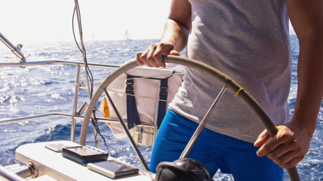 slo mo captain navigating a sailboat on the sea - sailing boat stock videos & royalty-free footage