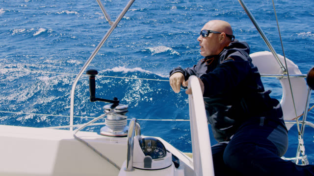 ws captain navigating a sailboat on the sea - sailing team stock videos & royalty-free footage
