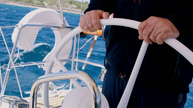 ws captain navigating a sailboat on the sea - helm stock videos & royalty-free footage