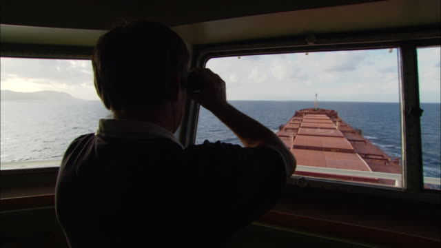 a captain of a barge looks through binoculars out the bridge's window. - captain stock videos & royalty-free footage