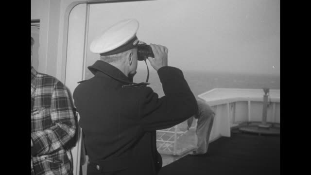 Captain on bridge of SS United States uses binoculars / smokestacks / passengers on deck chairs on enclosed deck / passengers stroll by / library...