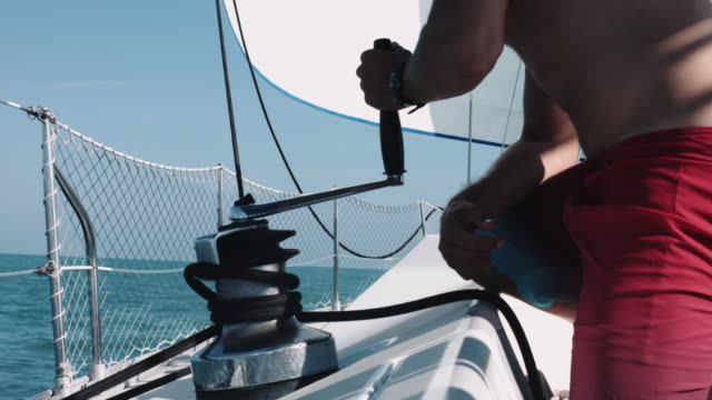 captain on sailboat adjust sail ropes - captain scarlet stock videos and b-roll footage