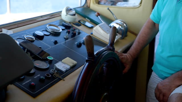 Captain Turns Boat Steering Wheel at Instrument Control Panel