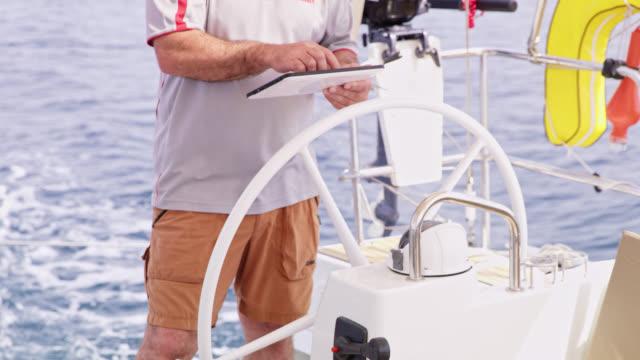 海の上のヨットを移動しながらタブレットを使用して ws キャプテン - 操作する点の映像素材/bロール