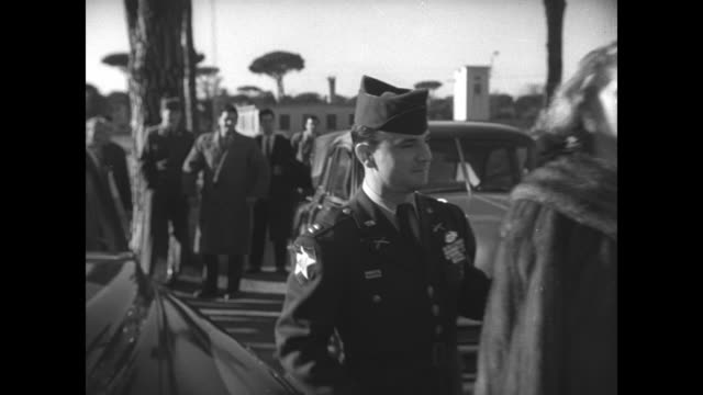 """caption """"livorno"""" superimposed over car arriving at camp darby, a us army base in livorno, italy / photographers take photos / actress sophia loren... - sophia loren stock videos & royalty-free footage"""