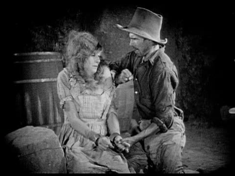 1926 b/w ms captive woman (charlotte stevens) shaking her head at man (danny hoy) who pushes her / usa - gewalt stock-videos und b-roll-filmmaterial