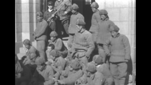 stockvideo's en b-roll-footage met captured chinese army soldiers sit on ground / south korean guards watch over chinese pows who wear quilted winter gear as they stand in doorway / vs... - south korean army