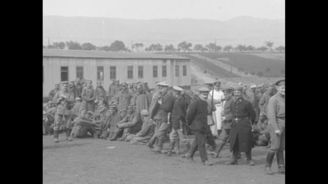 Captured Russian soldiers milling around on the grounds of Brest Fortress one with an extremely long bayoneted rifle / Note exact month/day not known