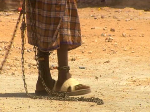 Captured Somali pirate walks along prison grounds with chained ankles 17 June 2009