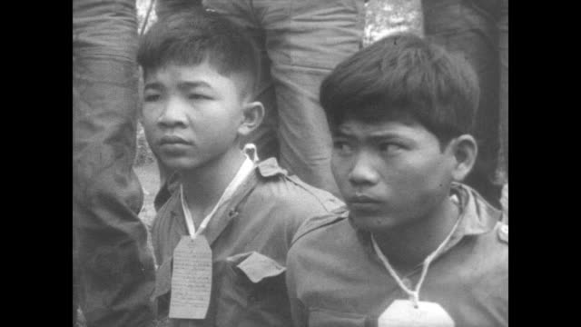 Captured Viet Cong prisoners sitting on the ground hands behind their backs with tags hanging off their shirts / soldiers stand behind the very young...