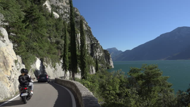 Car and scooter on Gardesana Occidentale lakeside road at Lake Garda