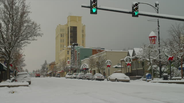WIDE ZOOM IN car and two people on snowy street decorated for holidays during snowfall in downtown Ashland, Oregon