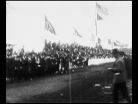 ls car approaches crosses finish line at 1906 vanderbilt cup race in nassau county new york / race official stands in front of crowd on turn of... - 1906 stock videos and b-roll footage