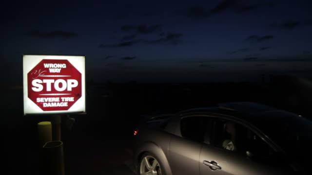 Car approaches lighted sign, dusk sky
