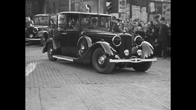 Car approaches passes bearing King George VI Queen Elizabeth and Eleanor Roosevelt as it leaves Stepney crowds line street wave