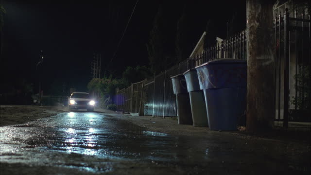 WS Car approaching through wet road and turning away / Los Angeles, California, USA