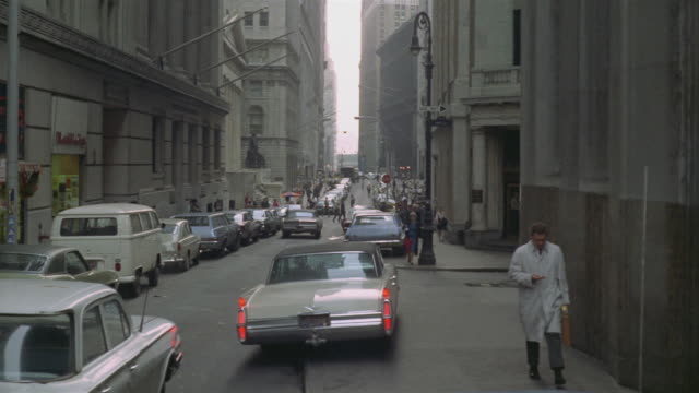 1969 WS Car attempting to park on Wall Street sidewalk / Manhattan, New York