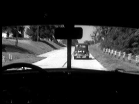 stockvideo's en b-roll-footage met 1935 ms pov car attempting to pass another car on a hill/ oncoming car forces car back into lane - 1935