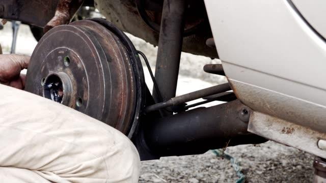 autoband bremsen reparatur - hispanic mann disassembling trommel - stahlfass stock-videos und b-roll-filmmaterial