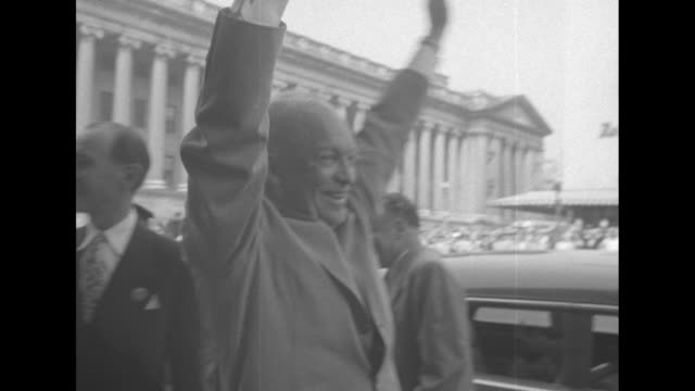 car bearing republican party presidential candidate dwight d. eisenhower pulls up to curb, with crowd of supporters on sidewalk / eisenhower, outside... - ロナルド レーガン ワシントン国際空港点の映像素材/bロール