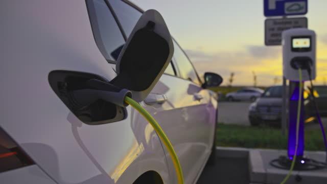 vidéos et rushes de slo mo voiture chargée à la station de recharge du véhicule électrique - parking