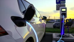 SLO MO Car being charged with blue energy going through EV cable