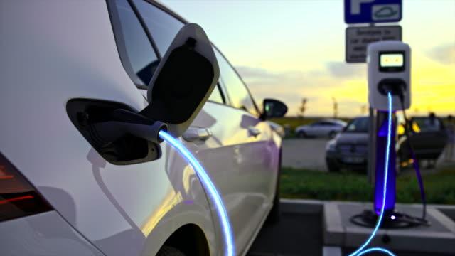 vídeos de stock, filmes e b-roll de slo mo car sendo carregado com energia azul passando por cabo ev - estação