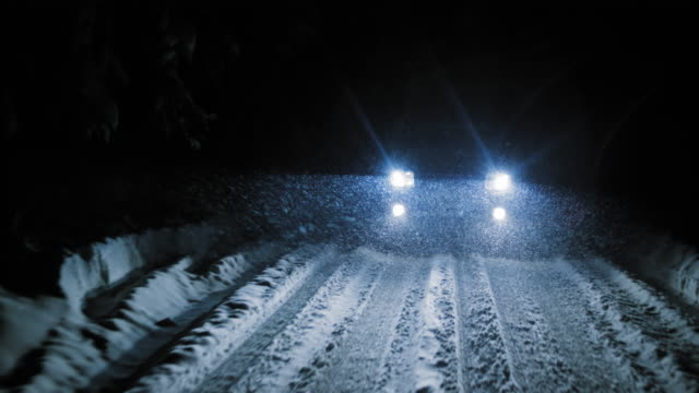 Car being driven at night on snowy road in snowfall