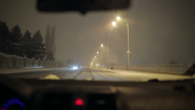 Car being driven on a snowy night.