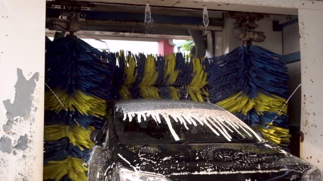bil som soaped och tvättas av auto maskin. - biltvätt bildbanksvideor och videomaterial från bakom kulisserna