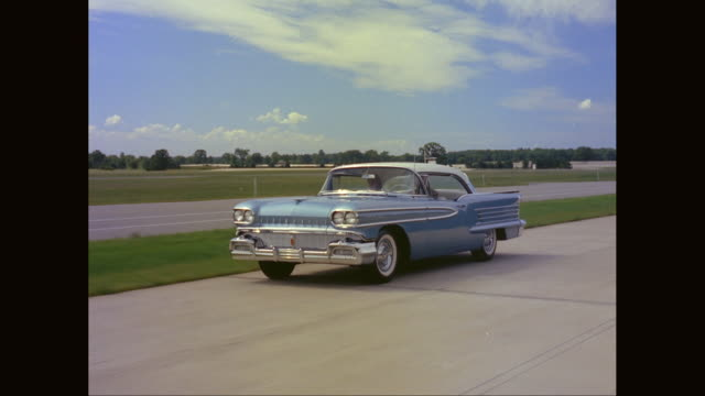 ws ts car - blue oldsmobile moving on road / united states - vintage car stock videos and b-roll footage
