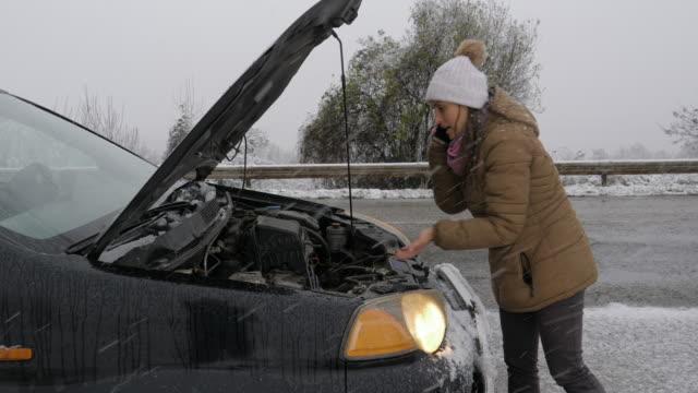 vídeos de stock, filmes e b-roll de quebra de carro na primeira neve. problemas de carro no meio do nada com mau tempo. seguro de carro. uma mulher na estrada. - margem de estrada