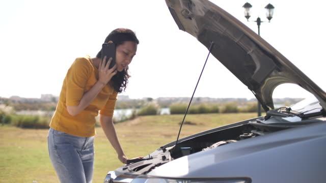 ラジエーターボンネットを開く道路の女性に故障した車、車の喫煙車のエンジンはパニックと混乱を引き起こす - 自動車事故点の映像素材/bロール