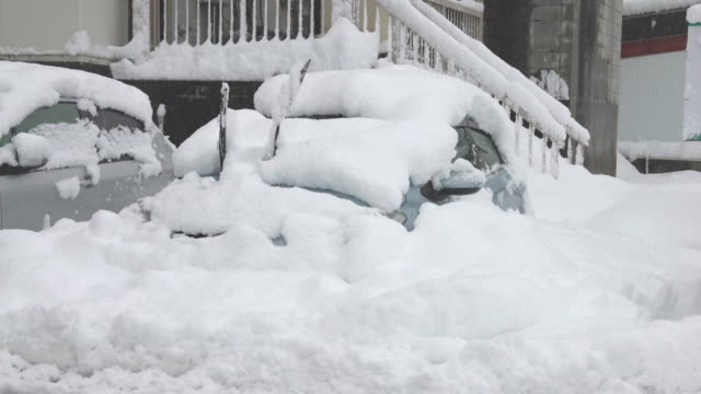 vídeos de stock e filmes b-roll de car buried in snow after a major winter storm hits northern japan - enterrado
