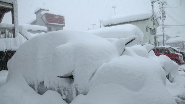 vídeos de stock e filmes b-roll de car buried under deep snow after massive blizzard hits northern japan - enterrado