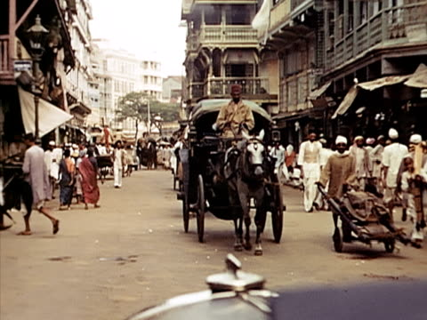 1939 ws car pov of busy street scene with people and animals/ bombay, india  - reportage stock videos and b-roll footage