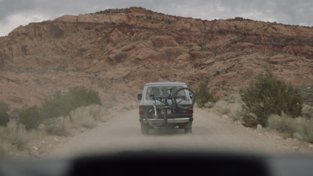 stockvideo's en b-roll-footage met car pov. caravan of friends on moab road trip drive down winding dirt road. - grind