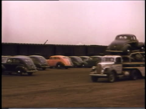 1940 car carrier truck full of fords driving in parking lot - ford truck stock videos and b-roll footage