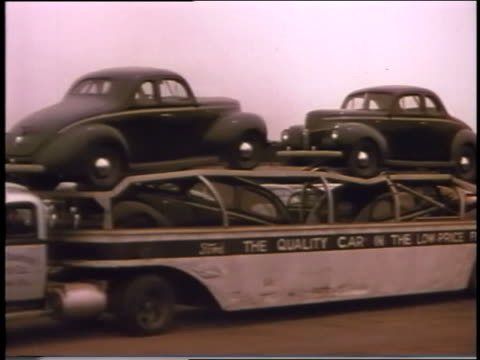 1940 pan car carrier truck full of fords passing camera - ford truck stock videos and b-roll footage