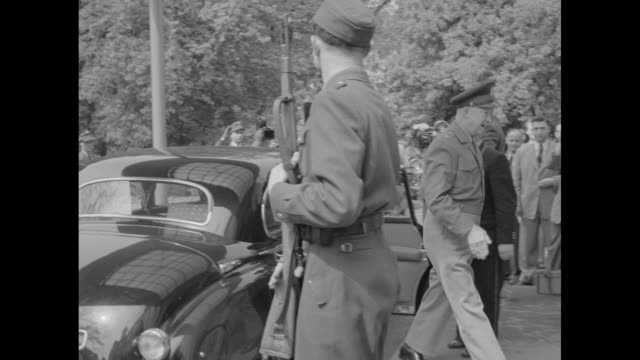 Car carrying Gen Dwight Eisenhower Supreme Commander of NATO pulls up and stops he gets out of car and is greeted by officials / he walks through...